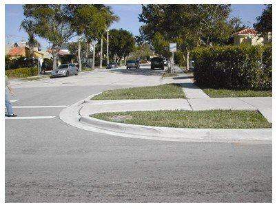 A sidewalk that meets the street in one direction but requires pedestrians to backtrack to continue with a left or right turn